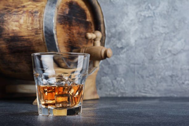 Scotch whisky with ice cubes in old fashion glass and vintage wooden barrel Strong alcoholic drink scotch whisky with ice cubes in old fashion glass and vintage wooden barrel in cellar on gray concrete background brandy stock pictures, royalty-free photos & images