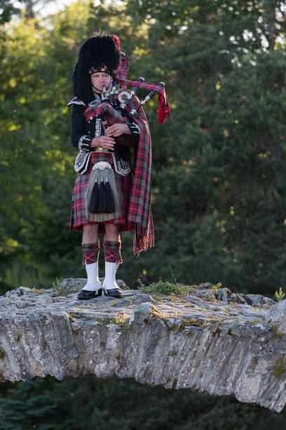 Scotland, Europe, bagpipes A Scottisch man playing on a bagpipe on an old stone bridge in Inverness, Scotland. Picture made on 06-24-2018 inverness scotland stock pictures, royalty-free photos & images