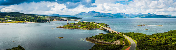 Scotland Skye Bridge over Loch Alsh to Highlands mountains panorama The Skye Bridge arching over Loch Alsh and the historic Kyleakin lighthouse on Eilean Ban overlooked by the dramatic mountain peaks of the Red Cuillin deep in the Highlands of Scotland. ProPhoto RGB profile for maximum color fidelity and gamut. isle of skye stock pictures, royalty-free photos & images