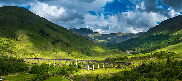 Scotland sunlight on Highland mountain glen Glenfinnan viaduct panorama Lochaber Summer sunlight illuminating the iconic arches of the Gelnfinnan Viaduct as it curves across the green glen at the end of Loch Shiel overlooked by the rugged mountain peaks of the Highlands, Scotland. ProPhoto RGB profile for maximum color fidelity and gamut. scottish highlands stock pictures, royalty-free photos & images