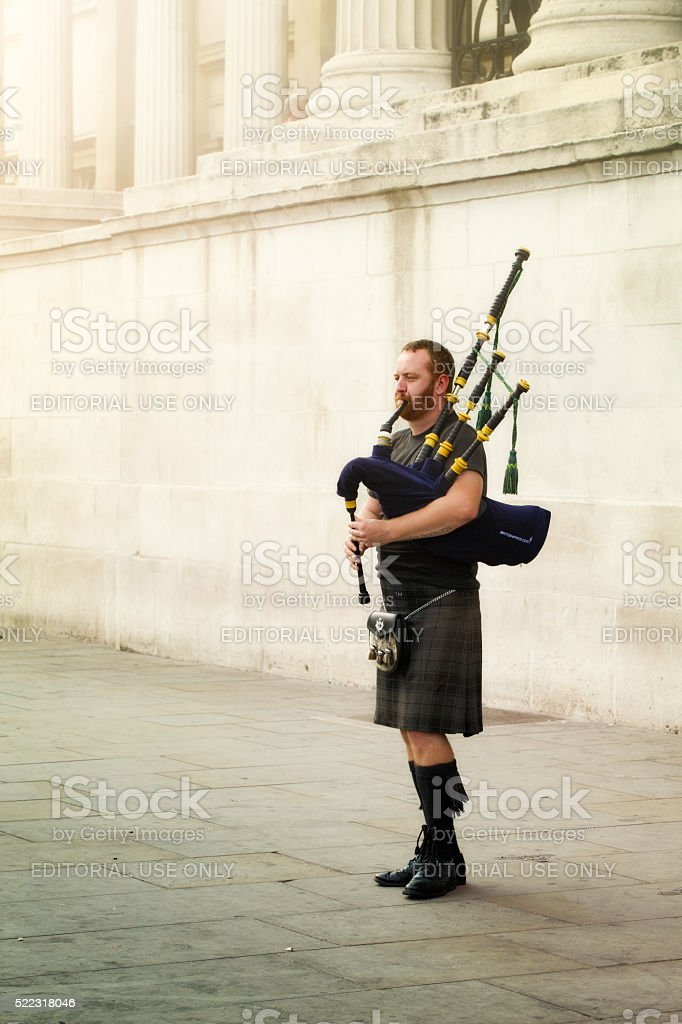 Scottish bagpipe player street of London foggy day stock photo