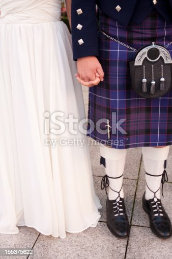 Scottish bride and groom in formalwear, including wedding gown and kilt.