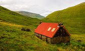 A red roofed barn in the wilderness of the Scottish highlands.