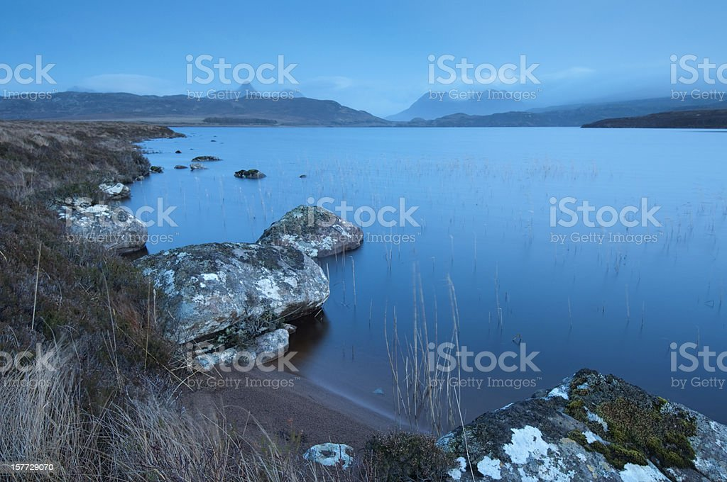 Scottish loch (lake) and highland mountains after sunset (blue hour) royalty-free stock photo