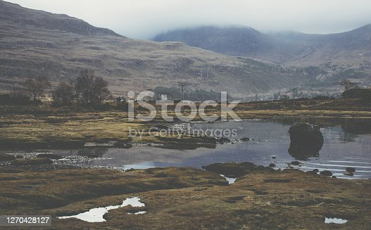 In the Scottish mountains, sky reflected in the water of bog and marsh land with a misty atmosphere