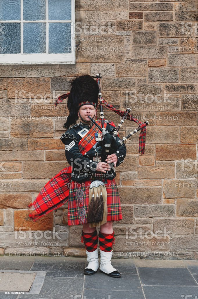 A Scottish piper man dressing in Scottish traditional tartan kilt playing a bagpiper at Royal Mile, touristic street of Old Town Edinburgh City in Scotland, UK stock photo
