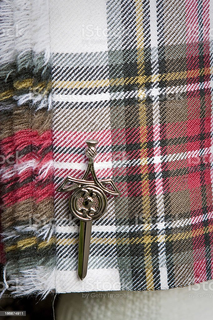 Scottish sword pin on red and white kilt stock photo