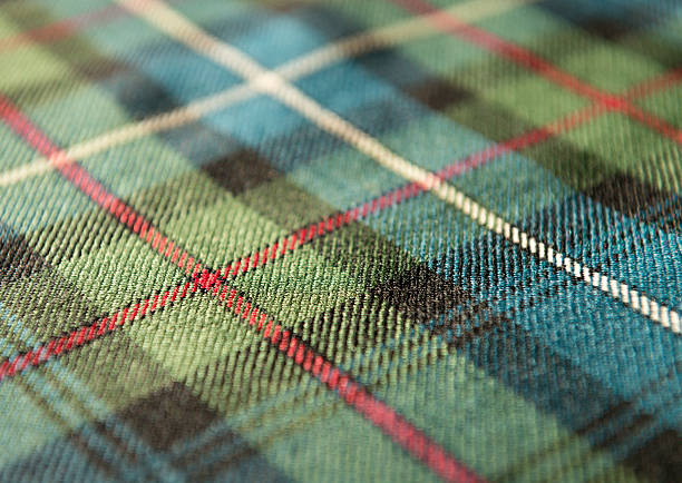Scottish tartan pattern Macro image showing the woven woolen design of a traditional Scottish tartan fabric, for use as a kilt or other garment. plaid stock pictures, royalty-free photos & images