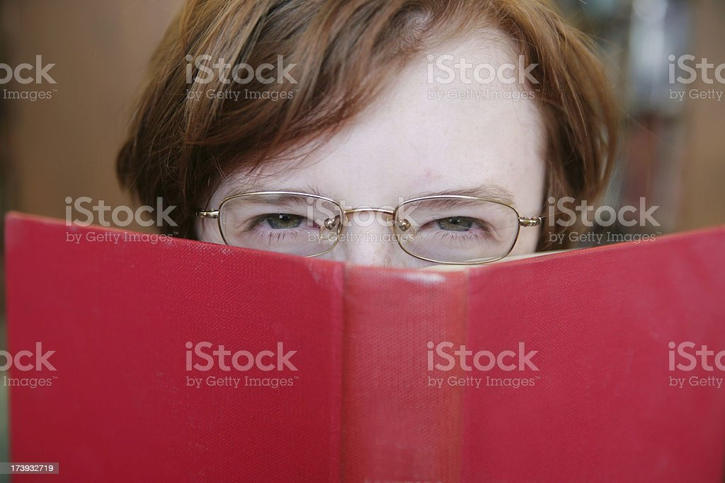 Scowling Teen Reading a Book royalty-free stock photo