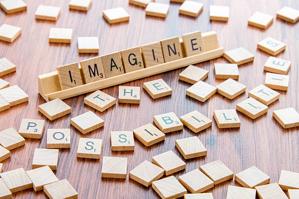 Scrabble Word Game wood tiles spelling IMAGINE THE POSSIBILITIES stock photo