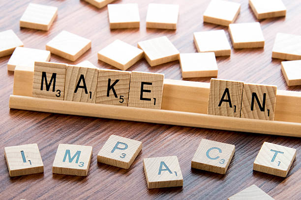 Scrabble Word Game wood tiles spelling MAKE AN IMPACT stock photo