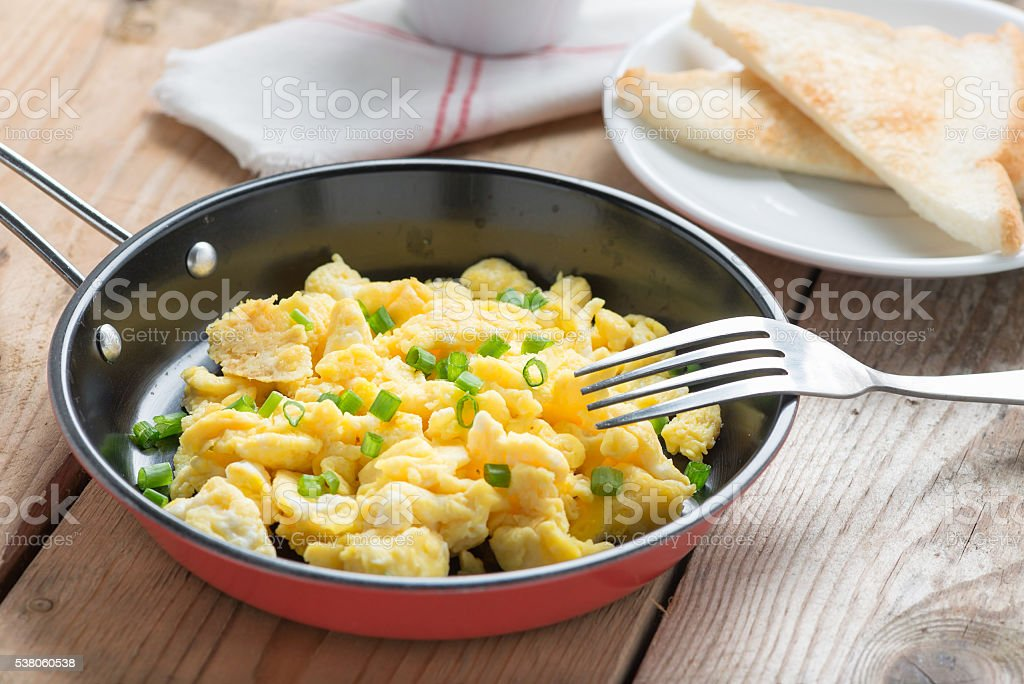Scrambled egg served in a pan with toast. stock photo