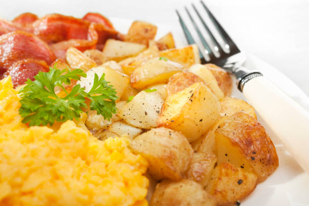 Scrambled Egg with Home Fries and Grilled Bacon stock photo