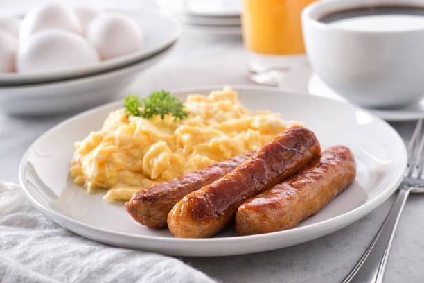 huevos revueltos y salchichas de desayuno - desayuno fotografías e imágenes de stock
