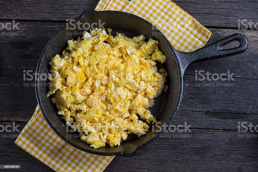 scrambled eggs in vintage frying iron pan, overhead view stock photo