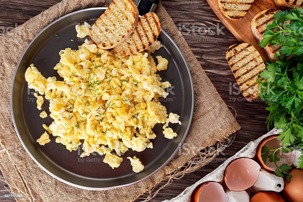 Scrambled eggs on Pan with grilled toast. stock photo