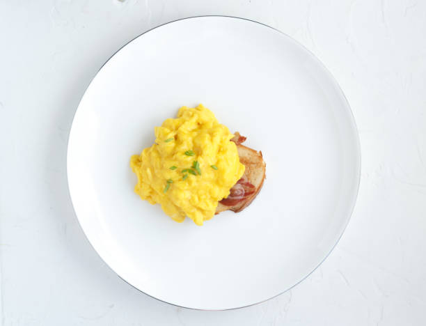 Scrambled eggs on plate over white stone background. Top view, flat lay stock photo