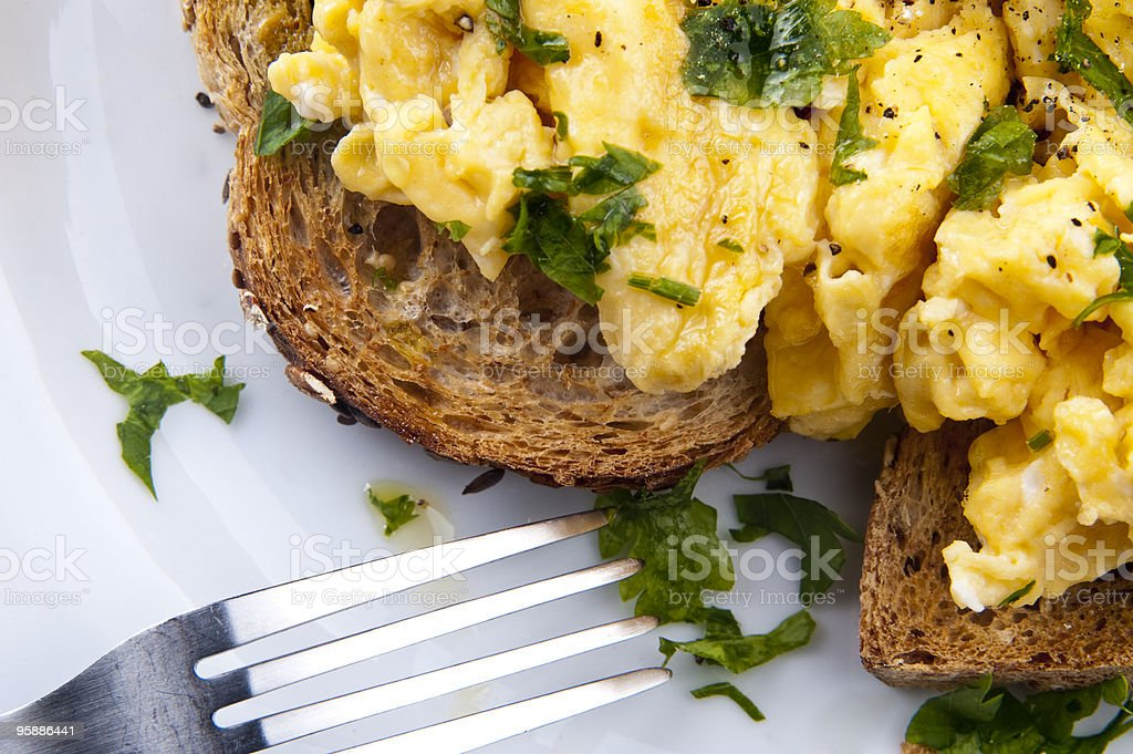 Scrambled eggs on toast shown with fork on a white plate stock photo
