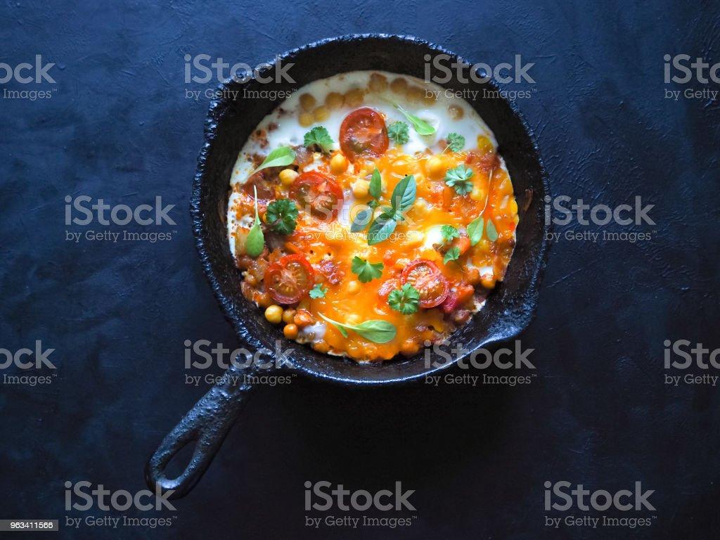 Œufs brouillés aux pois chiches et tomates sur une vieux poêle. Vue de dessus avec l'espace de la copie. - Photo de Aliment libre de droits