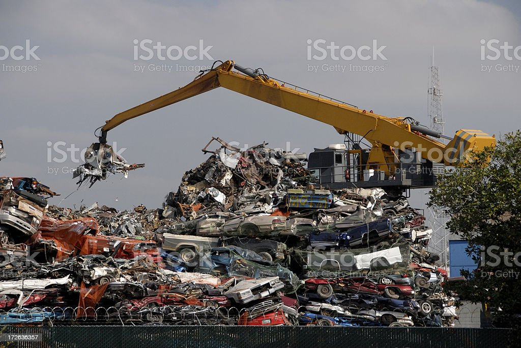 Scrap Metal In Jaws Of Crane At Recycling Center royalty-free stock photo