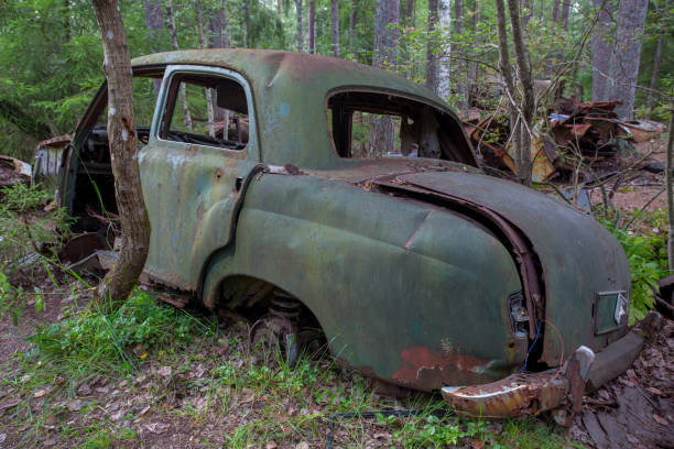 Scrap yard with old cars in forest in Ryd, Kyrko Mosse in Sweden stock photo