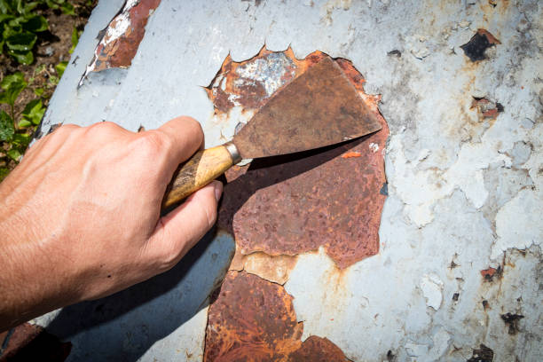 Scraping paint off rusted metal stock photo