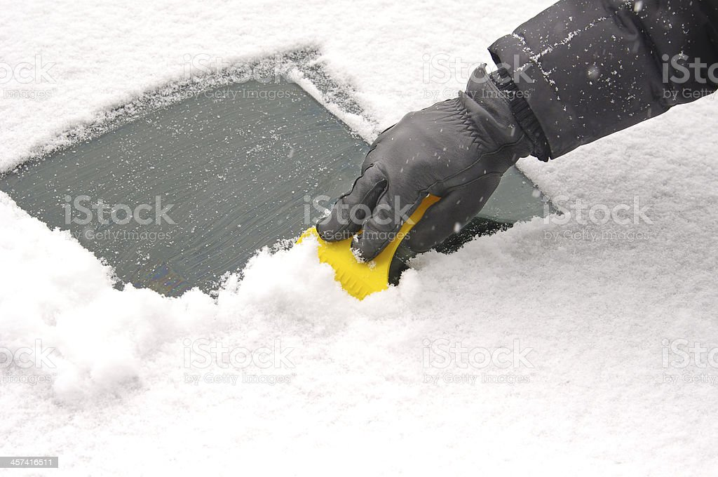 scraping snow and ice from the car windscreen stock photo