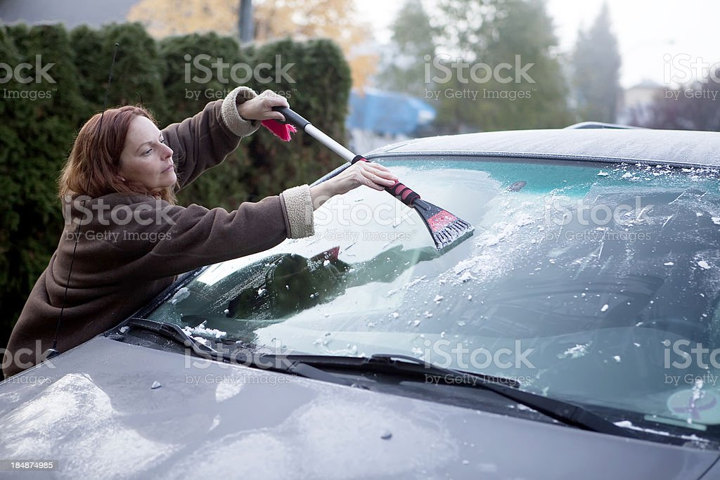 Scraping the van window on a frosty morning. royalty-free stock photo