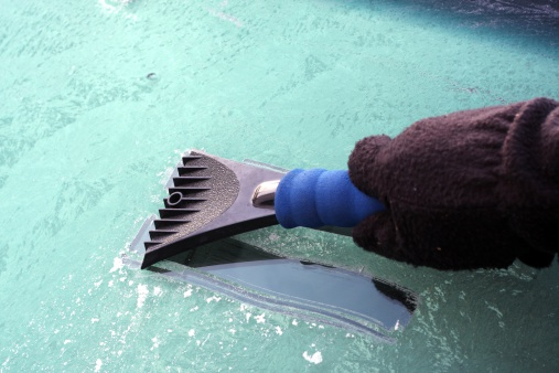 A driver wearing gloves scraping the ice off his windshield in the morning.