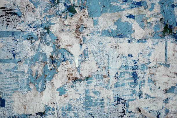 Scraps of old torn paper posters on the wall. Grunge urban background stock photo