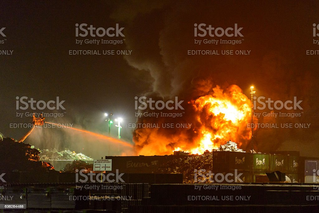 Scrapyard fire in an industrial area at night stock photo