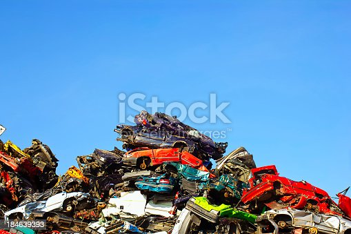 Scrapyard with crushed colorful cars with a blue sky in the background.
