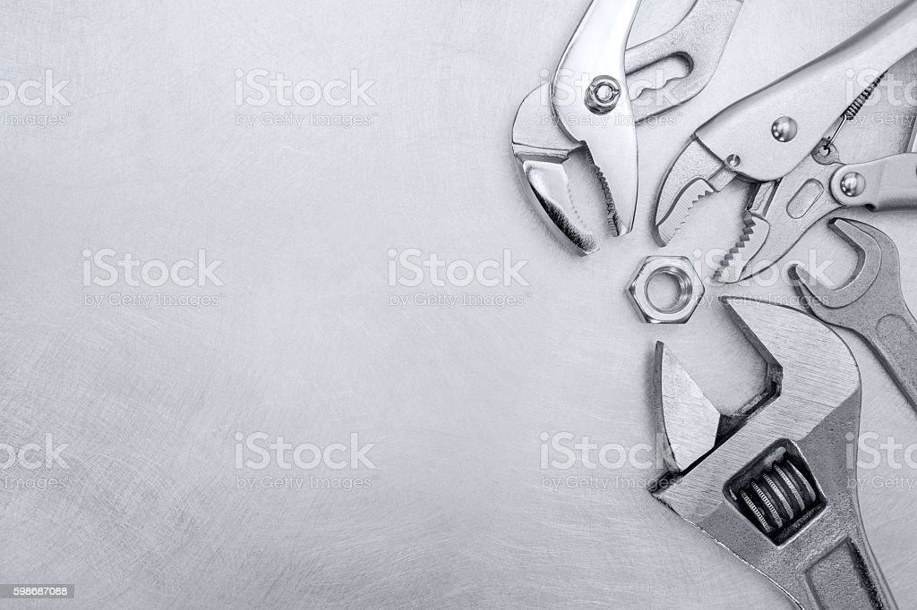 scratched grey metallic background with hand tools stock photo