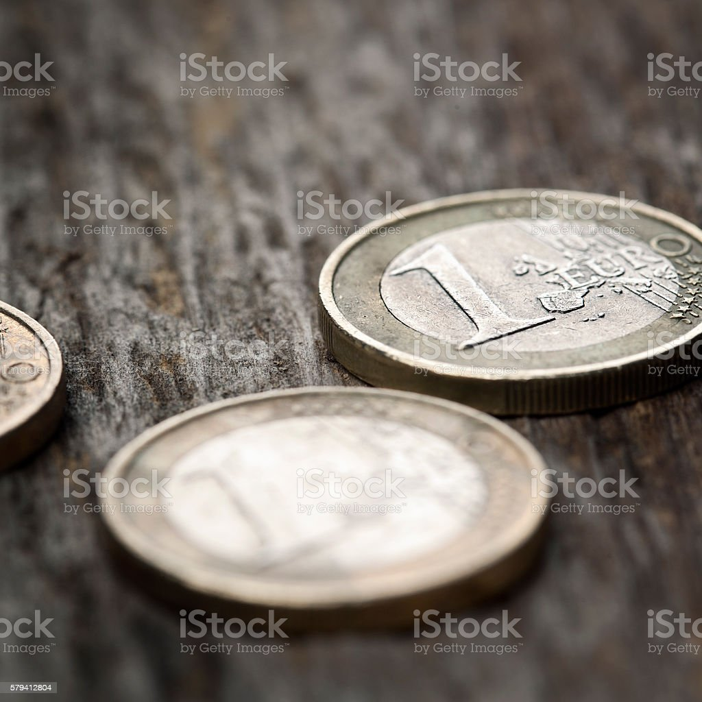 Scratched run-down euro coins on wooden background stock photo