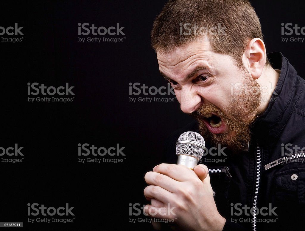 Scream of male angry rocker at the microphone royalty-free stock photo