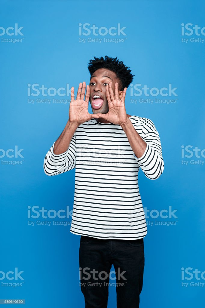 Screaming afro american young man Portrait of excited afro american guy wearing striped long sleeved t-shirt and black trausers, scraming. Studio shot, blue background.  Adult Stock Photo
