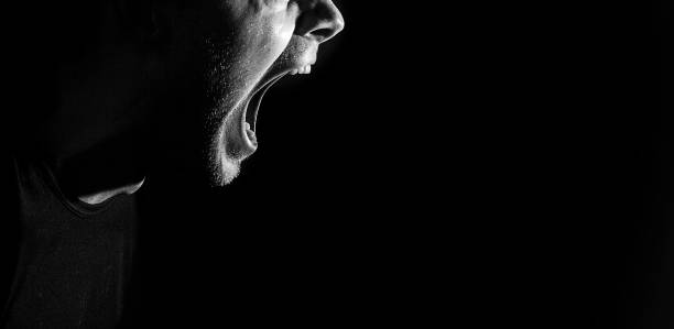screaming angry aggressive militant guy, man, black and white portrait, evil face, teeth stock photo