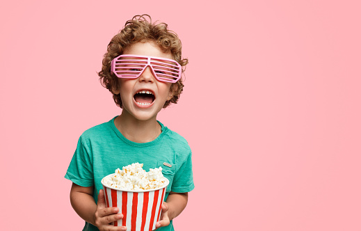 Curly kid in pink three-dimensional glasses holding basket of popcorn and screaming on pink background