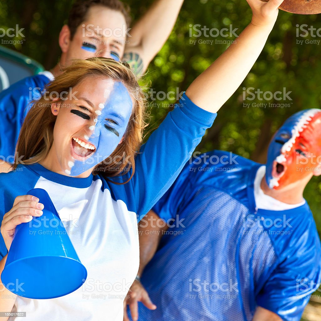 Screaming Fans With Faces Painted Showing Spirit at Tailgate Party royalty-free stock photo