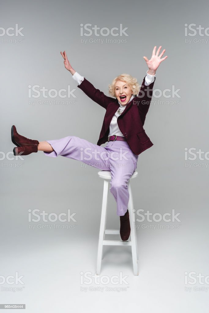 screaming funny senior woman sitting on chair with raised hands and leg on grey royalty-free stock photo