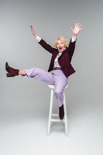 尖叫滑稽的資深婦女坐在椅子上舉起手和腿灰色 照片檔及更多 一個人 照片