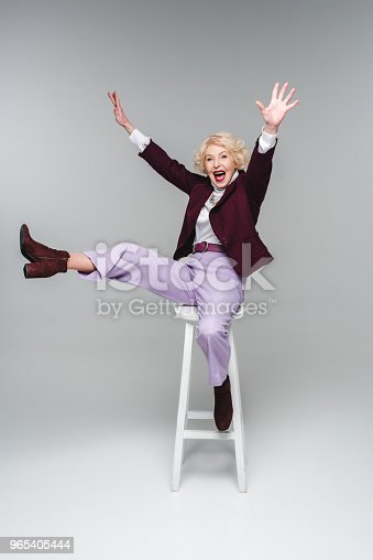 Screaming Funny Senior Woman Sitting On Chair With Raised Hands And Leg On Grey Stock Photo & More Pictures of Adults Only