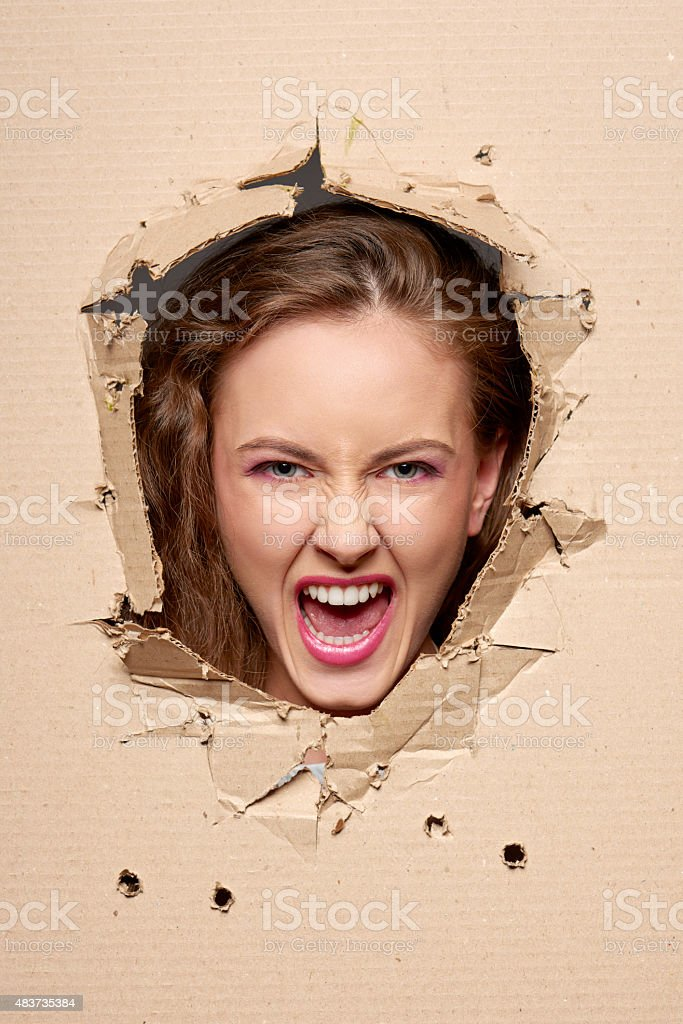 Screaming girl peeping through hole in paper stock photo