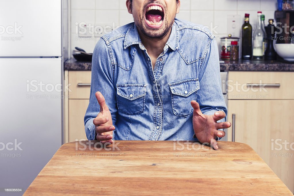 Screaming man gesturing with hands in his kitchen royalty-free stock photo
