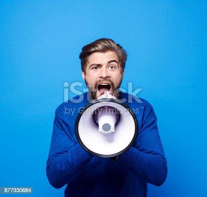 istock Screaming man with megaphone shouting 877330684
