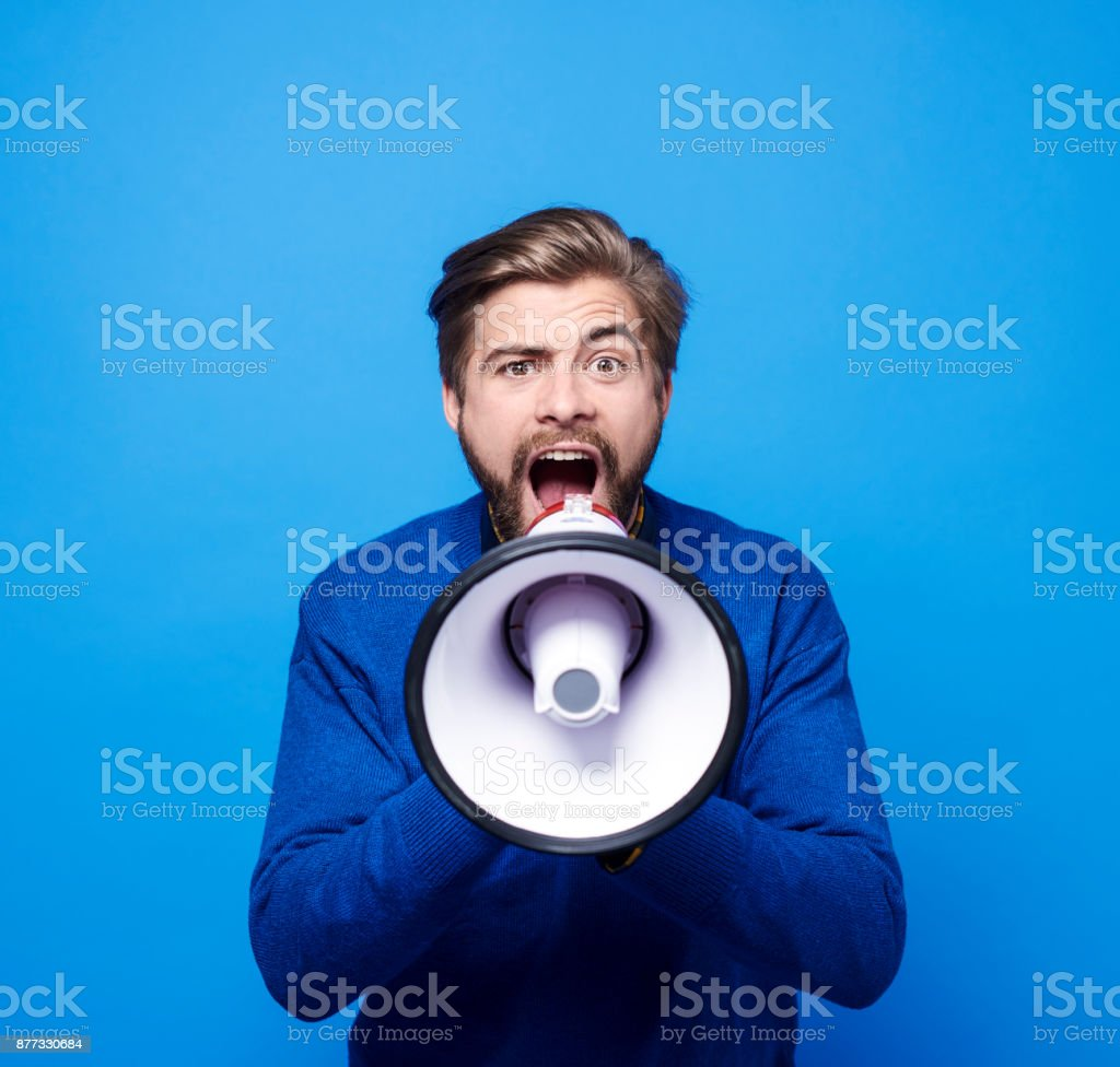 Screaming man with megaphone shouting stock photo
