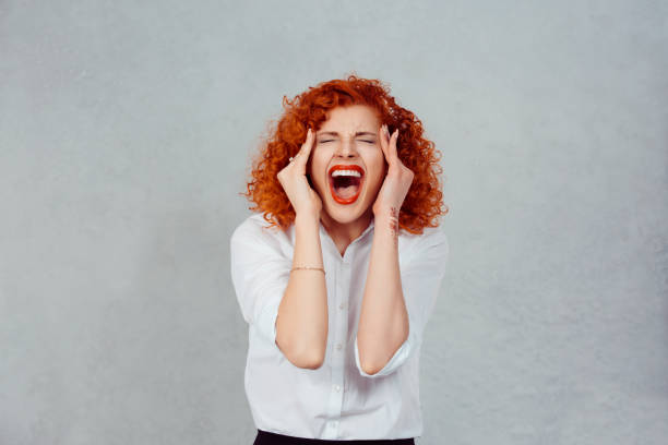 Screaming stressed. Portrait frustrated shocked redhead business woman yelling eyes closed hands on head temper tantrum isolated grey wall background. Negative human emotion facial expression reaction stock photo