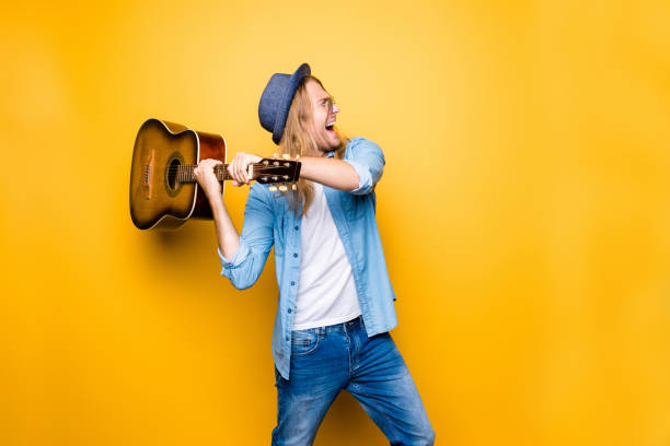screaming stylish guitarist can't write new songs anymore, he lost his inspiration, he is going to break the guitar - broken guitar stock photos and pictures