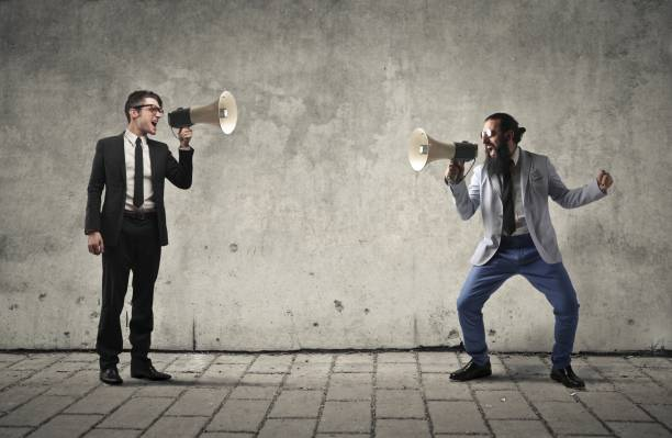 Screaming with each other Two man are screaming with each other with megaphones in their hands debate stock pictures, royalty-free photos & images