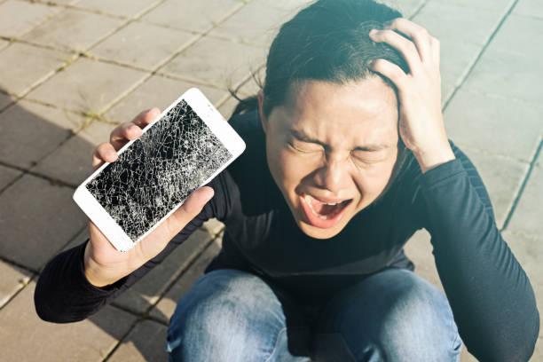 Schreiende Frau hält einen Bildschirm riss das Smartphone im Freien. – Foto